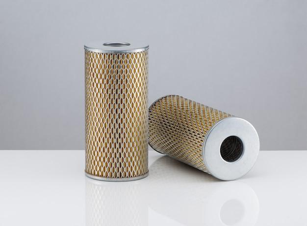 Forma cilíndrica de dois filtros automotivos em um fundo branco com reflexo