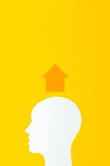 Forma da cabeça com seta em fundo amarelo