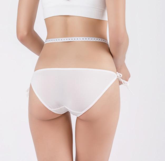 Forma das mulheres ela está usando um medidor de cintura.