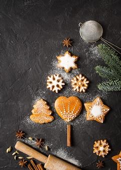 Forma de abeto de pão de gengibre em fundo preto, conceito de natal e feliz ano novo, vista superior do espaço de cópia, vertical