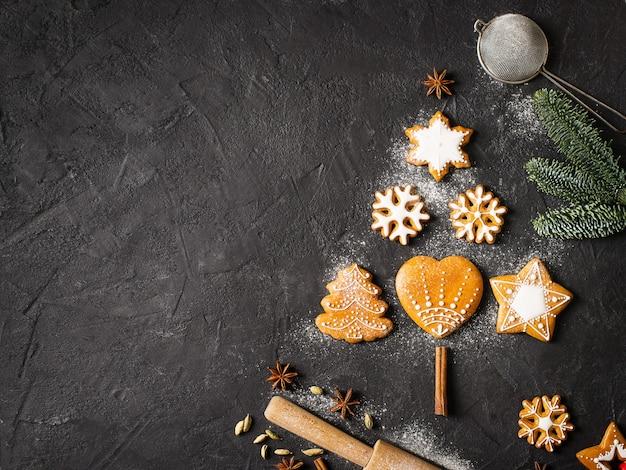 Forma de abeto de pão de gengibre em fundo preto, conceito de natal e feliz ano novo, vista superior do espaço de cópia,