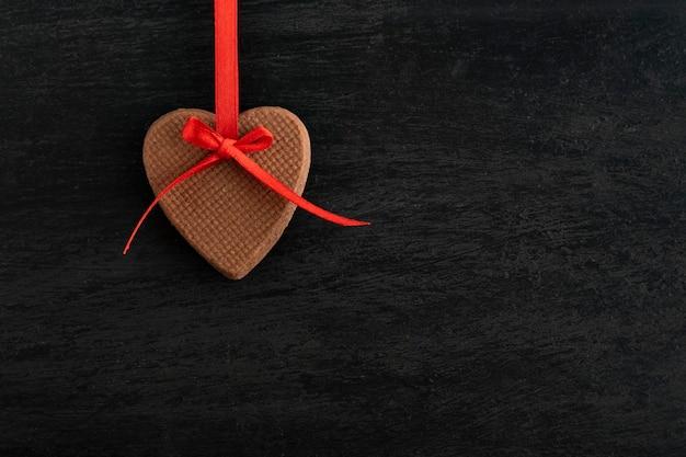 Forma de biscoitos caseiros de corações com fita vermelha na superfície preta. dia das mães