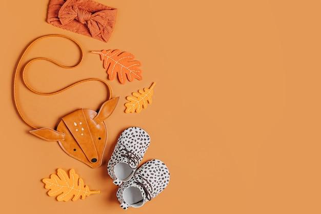 Forma de bolsa de crianças de cervo bonito, botas de bebê e folhas de outono. conjunto de acessórios de moda infantil para o outono. camada plana, vista superior