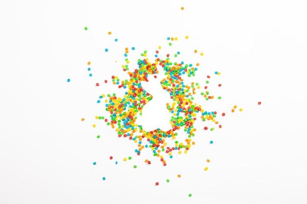 Forma de coelhinho da páscoa e decoração multicolorida sobre uma superfície de luz. conceito de páscoa, ano novo. minimalismo. vista plana, vista superior