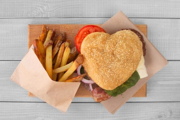 Forma de coração, amor, hambúrguer e batatas fritas, conceito de hambúrguer fast food, jantar surpresa do dia dos namorados, fundo de madeira, vista superior plana lay