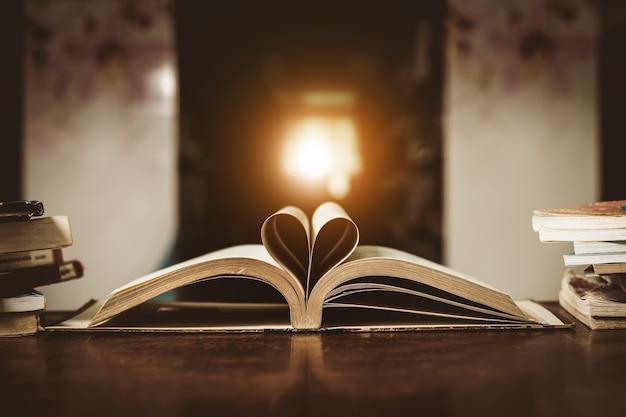 Forma de coração bonito no meio do livro com luz do sol para o fundo