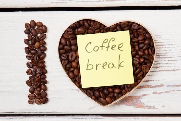 Forma de coração com feijão e pausa para o café escrito na etiqueta. eu amo o conceito de café. vista do topo.