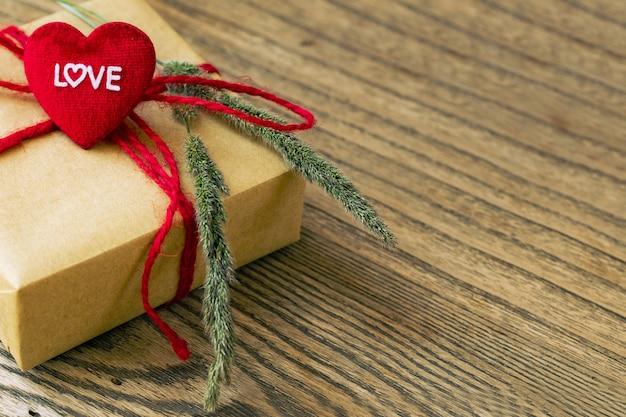 Forma de coração com palavra de amor, caixa de presente e flor