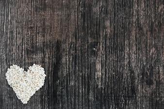 Forma de coração de arroz feita no pano de fundo preto de madeira
