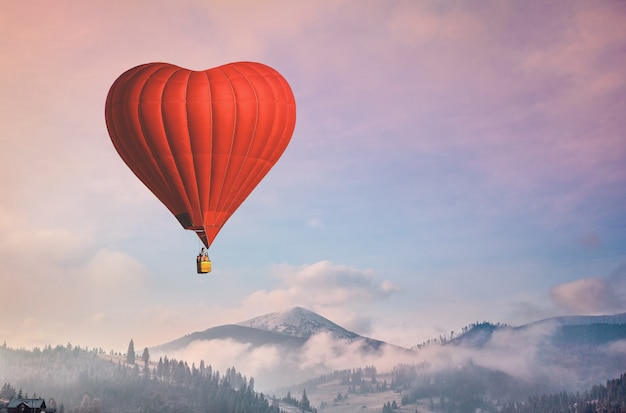 Forma de coração de balão de ar vermelho contra céu azul e rosa pastel em uma manhã ensolarada e brilhante.