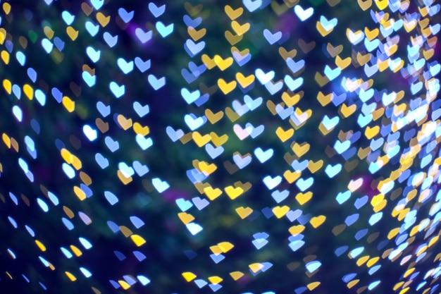 Forma de coração de borrão amarelo laranja. luz noturna em árvore no jardim