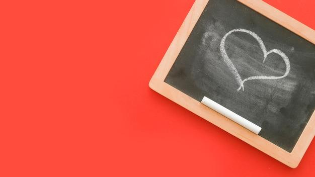Forma de coração de chalkdrawn em ardósia sobre fundo vermelho