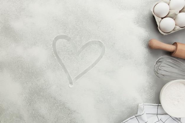 Forma de coração de farinha no plano de fundo de concreto cinza, copie o espaço. ingredientes de panificação, utensílios de cozinha, conceito de passatempo de cozinha. prepare a massa, o ovo, a farinha de tigela, o rolo, o batedor, o pano de prato