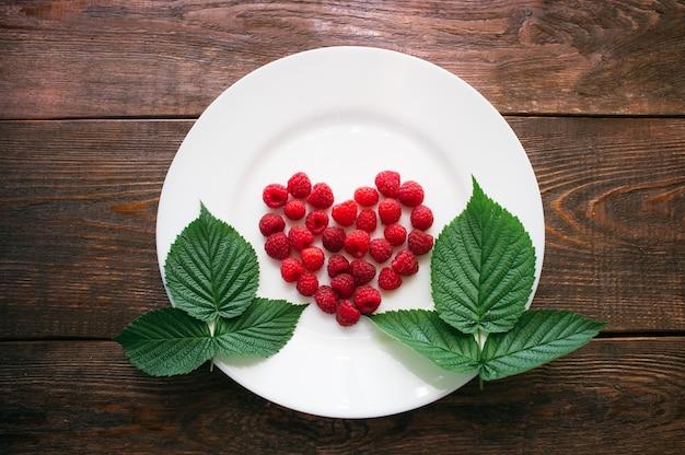 Forma de coração de framboesa nas folhas na mesa de madeira