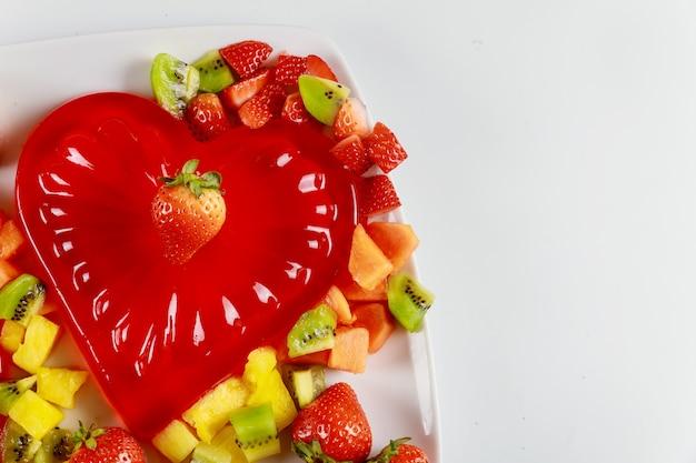 Forma de coração de gelatina vermelha com frutas frescas picadas