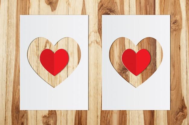 Forma de coração de papel com coração vermelho em fundo de madeira