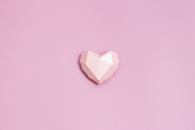Forma de coração de papel rosa poligonal em papel rosa. fundo de férias para o dia dos namorados.