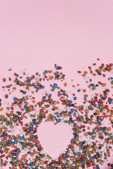 Forma de coração de pequenas pedras na mesa-de-rosa
