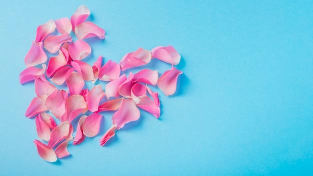 Forma de coração de pétalas de rosas na mesa