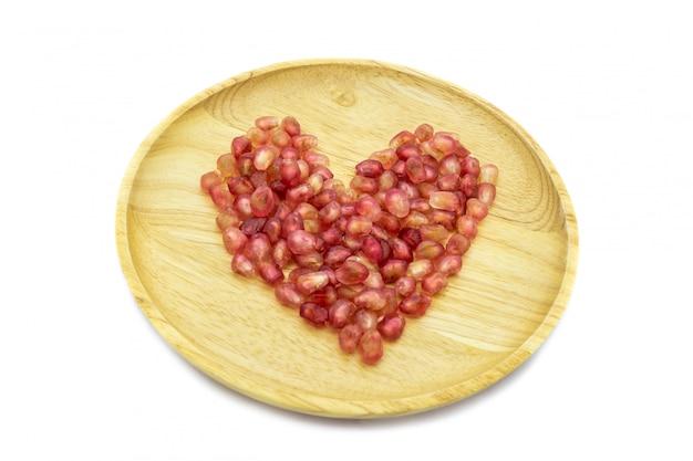 Forma de coração de romã fresca na placa de madeira, isolada no fundo branco