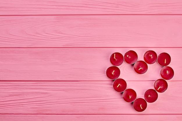 Forma de coração de velas, vista superior. projeto romântico de velas de luz de chá vermelho, espaço de cópia. idéia para decoração de feriado do dia dos namorados.