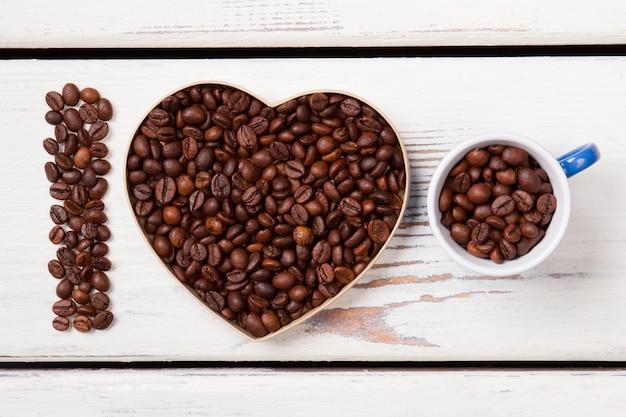 Forma de coração e xícara cheia de grãos de café torrados. eu amo café fresco natural. pranchas de madeira brancas na superfície.