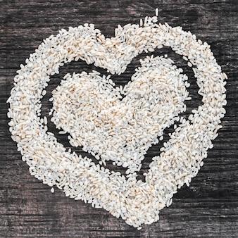 Forma de coração feita com arroz branco cru no cenário de madeira