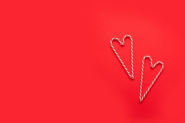 Forma de coração feita de bastão de doces de natal vermelho sobre fundo vermelho. conceito de ideia mínima
