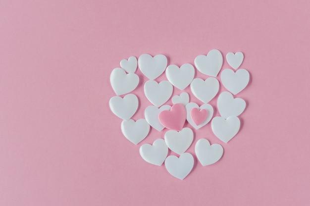 Forma de coração feita de corações de cetim brancos na rosa