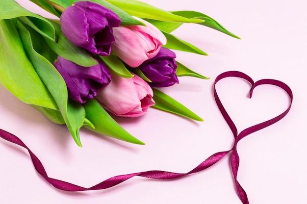 Forma de coração feita de fita roxa e buquê de tulipas roxas e rosa sobre um fundo rosa claro