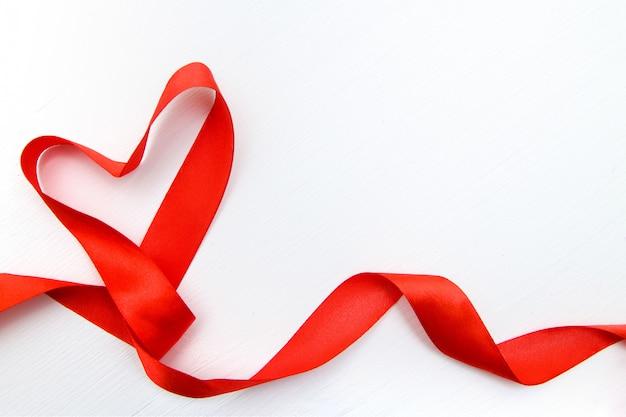Forma de coração feita de fita vermelha em fundo branco de madeira. copie o espaço