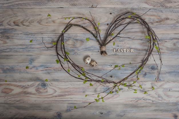 Forma de coração feita de galhos de bétula com letras páscoa e ovos de codorna