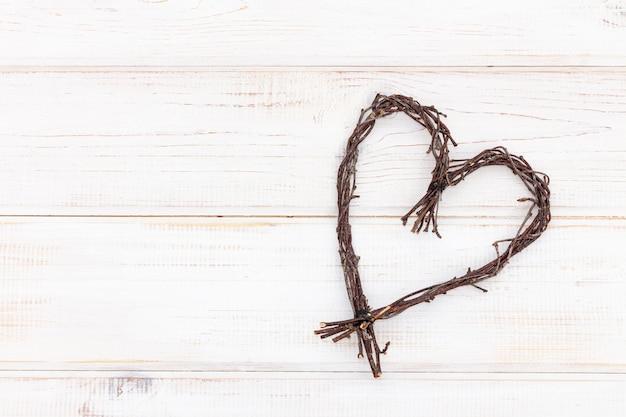 Forma de coração feita de galhos - símbolo de madeira do amor em um fundo branco.