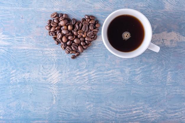 Forma de coração feita de grãos de café e xícara de café branca sobre fundo azul de madeira elegante