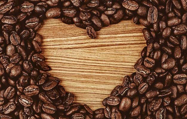 Forma de coração feita de grãos de café em superfície de madeira