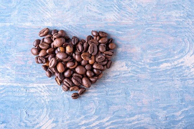 Forma de coração feita de grãos de café em um fundo azul de madeira elegante