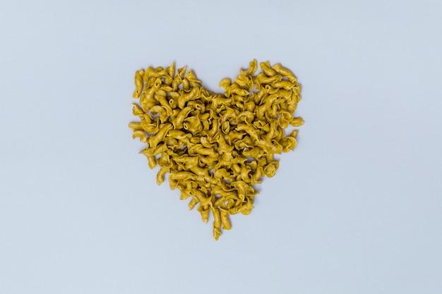 Forma de coração feita de macarrão cru italiano em fundo cinza