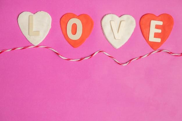 Forma de coração, palavra amor em corações vermelhos em fundo rosa, ícone de amor, dia dos namorados