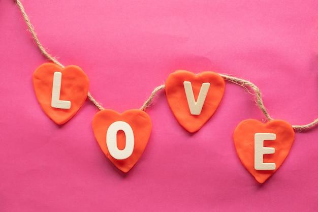 Forma de coração, palavra amor em corações vermelhos em fundo rosa