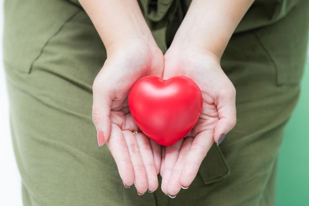 Forma de coração vermelho de borracha na mão de mulher bonita