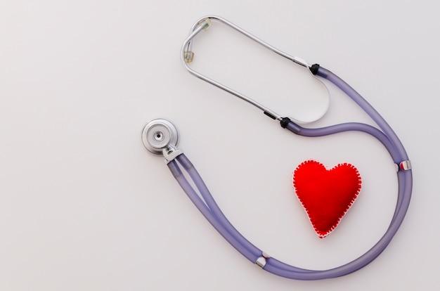 Forma de coração vermelho de têxteis com estetoscópio isolado no pano de fundo branco