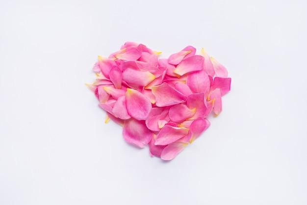 Forma de coração vermelho feita de pétalas de rosa cor de rosa em branco