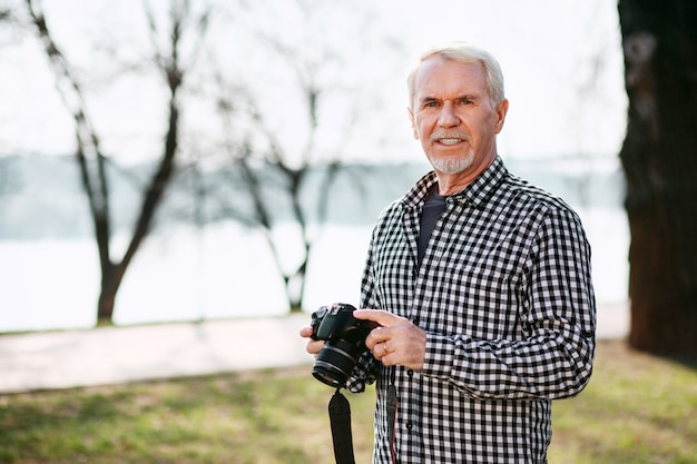 Forma de equipamento de câmera. homem sênior atraente posando ao ar livre e usando a câmera