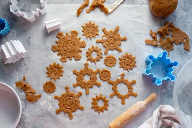 Forma de flocos de neve de biscoitos de cozimento de natal. massa crua, cortadores de biscoitos, rolo de massa.
