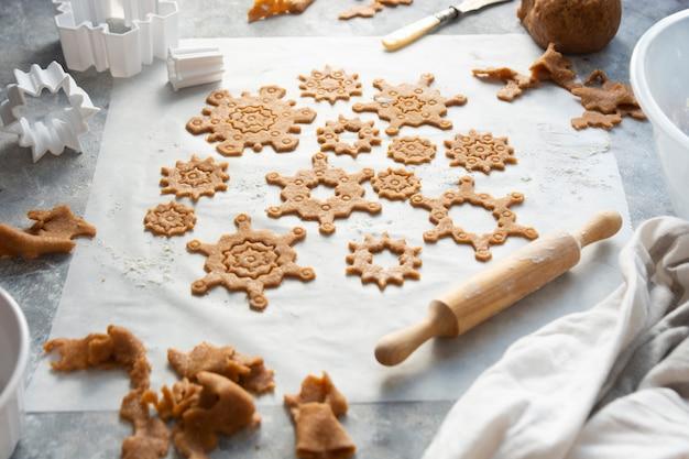 Forma de flocos de neve de biscoitos de natal. massa crua, cortadores de biscoitos, rolo de massa.