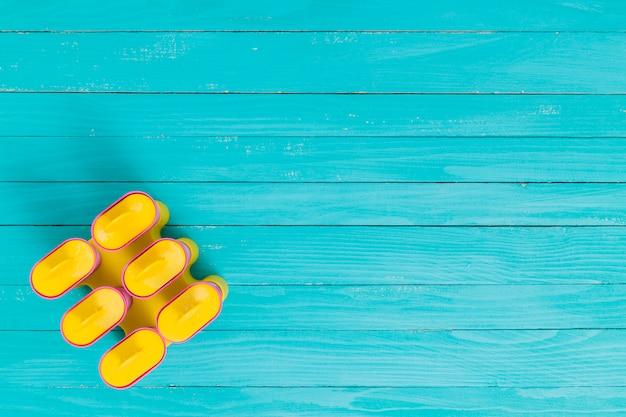 Forma de geada de picolé amarelo sobre uma superfície de madeira