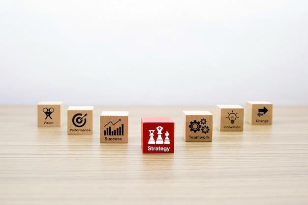 Forma de madeira do cubo com ícones de negócios para a estratégia e o conceito de sucesso.