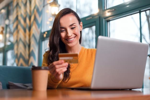 Forma de pagamento. mulher feliz e animada lendo o número do cartão de crédito enquanto olha para baixo e trabalha no laptop