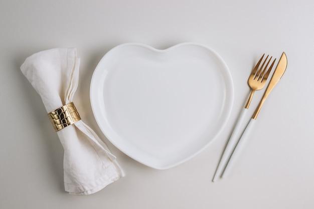 Forma de placa de coração e talheres de mesa romântica configuração
