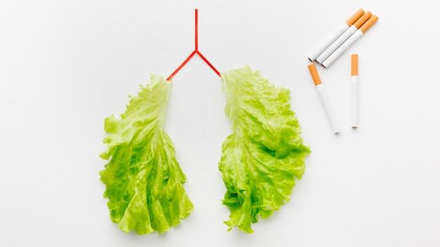 Forma de pulmões com salada verde e cigarros